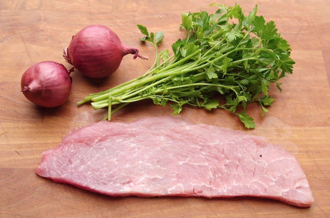 Fleisch für Wiener Schnitzel, bitte sorgfältig auswählen. Bild mit Schnitzel auf Brett mit schönem Umfeld.
