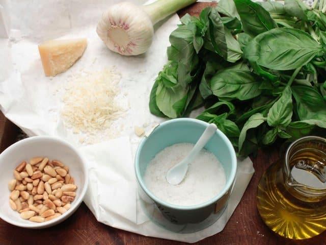 Die Zutaten für Pesto alla Genovese vorbereiten: fein geriebener Parmesan, geröstete Pinienkern, Salz, Basilikum, Olivenöl und Knoblauch