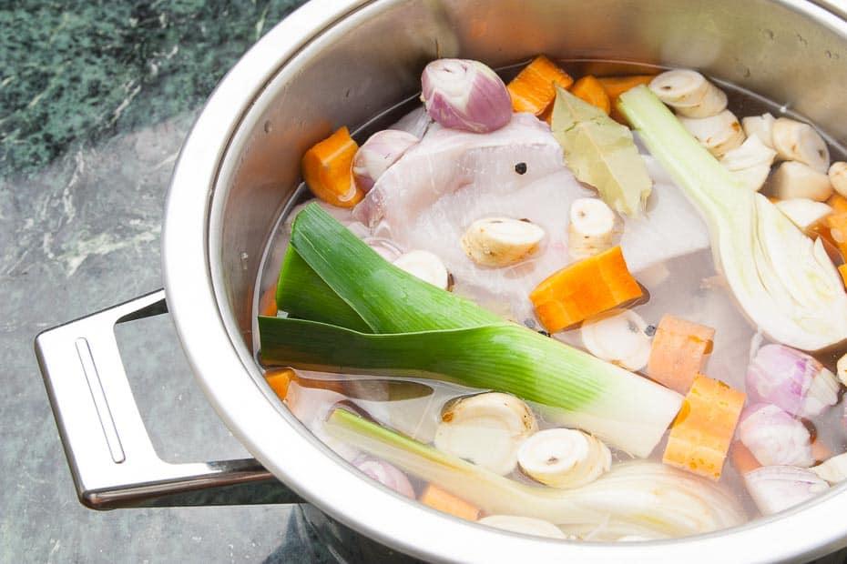 Fischfond mit Fischkarkassen und Gemüse im Topf.