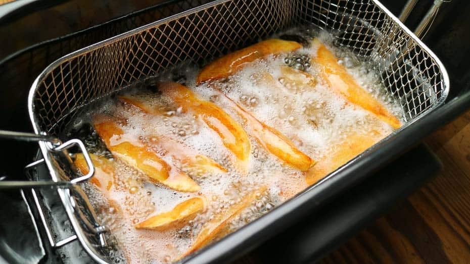 Pommes frites und Kartoffelspalten in der Fritteuse