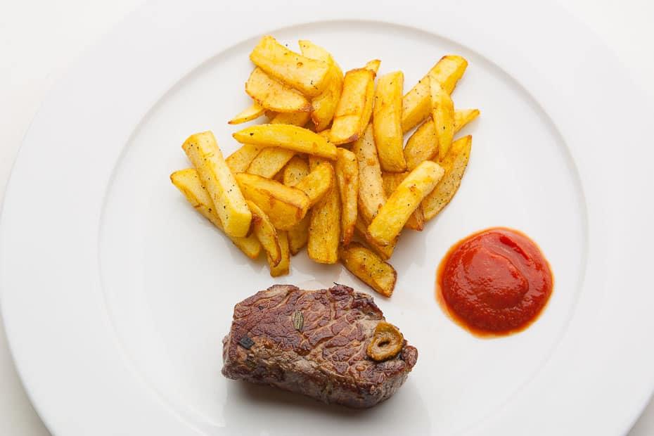 Pommes frites als Beilage, hier ein Steak mit Pommes und Ketchup.