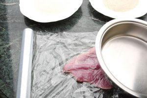 Schnitzel beim klopfen zwischen Frischhaltefolie