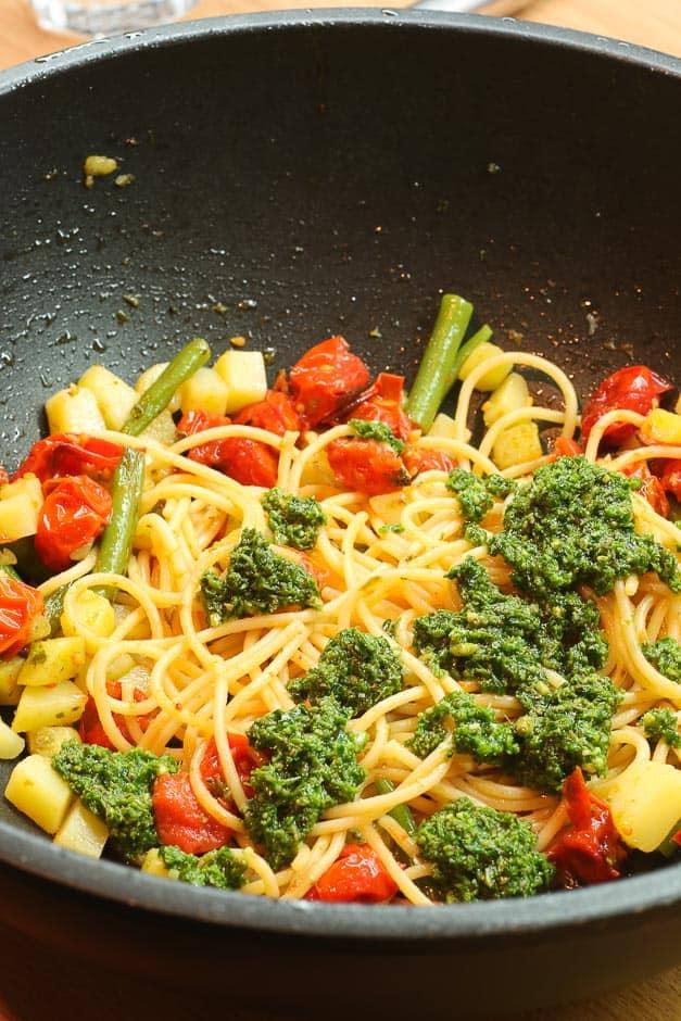Spaghetti mit Pesto Tomaten, Bohnen und Kartoffeln im Wok.