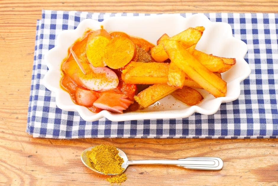 Currywurst sliced with currywurst sauce and french fries served