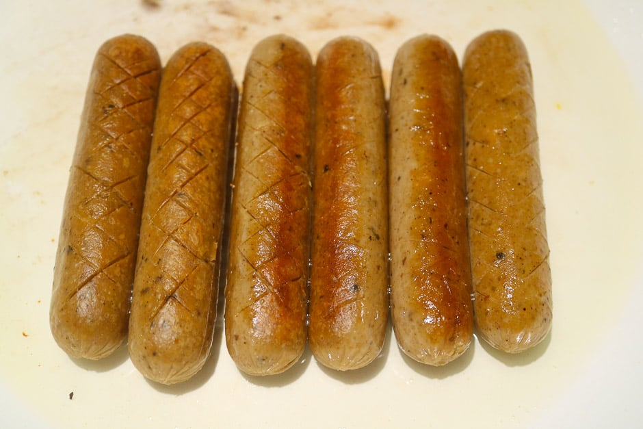 Fried sausages for currywurst in a pan.