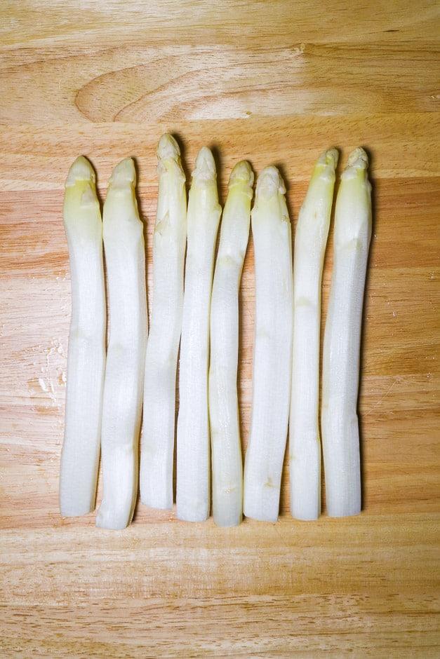 Peeled white asparagus on a board.