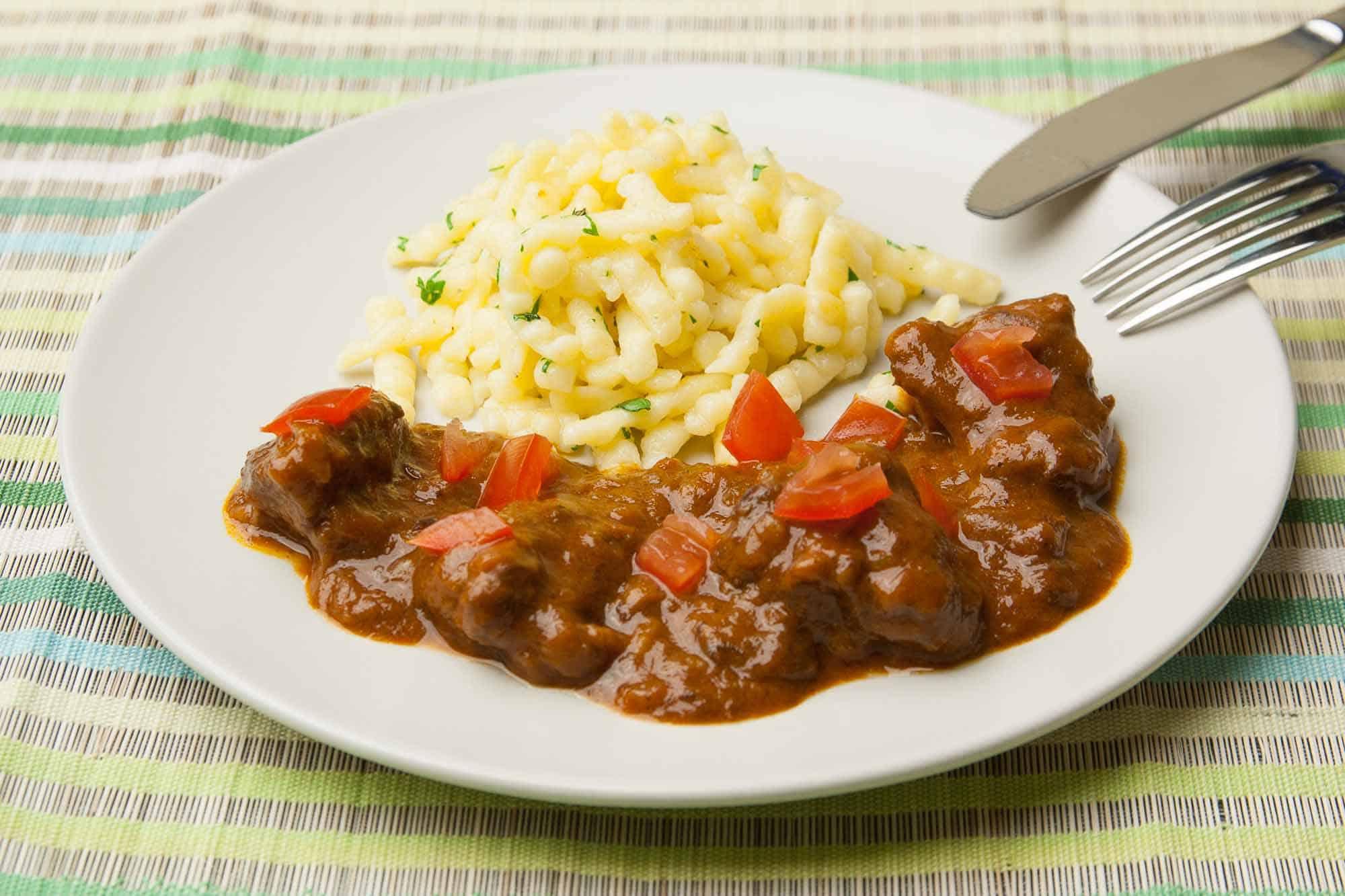 Rindergulasch serviert mit Spätzle, Petersilie und Tomatenwürfel