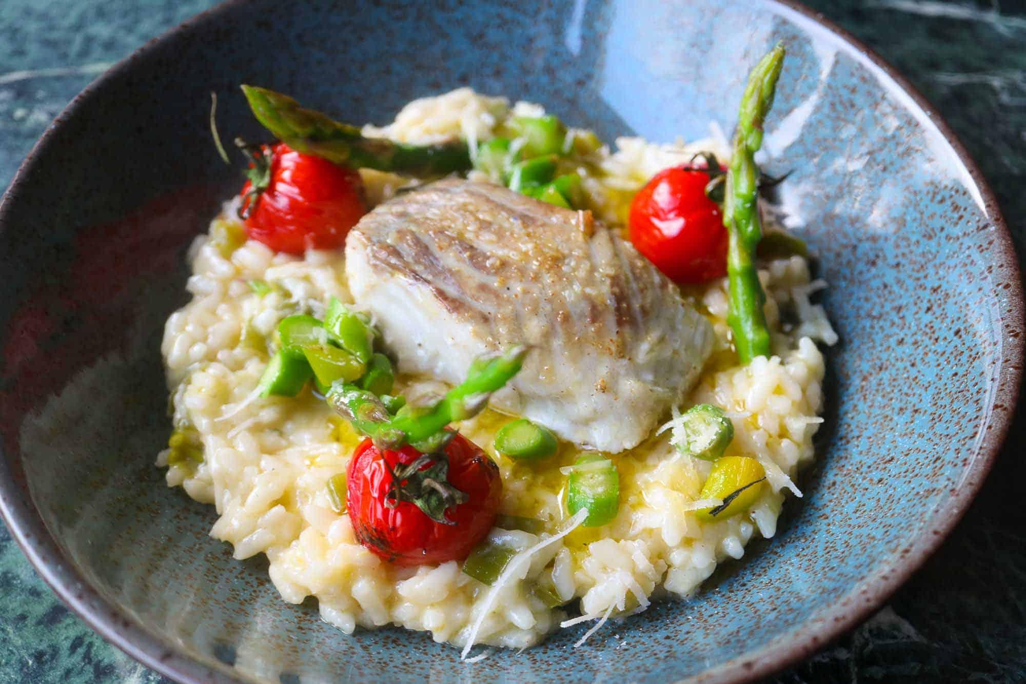 Zitronenrisotto serviert mit Spargel, tomaten und Seelachs.