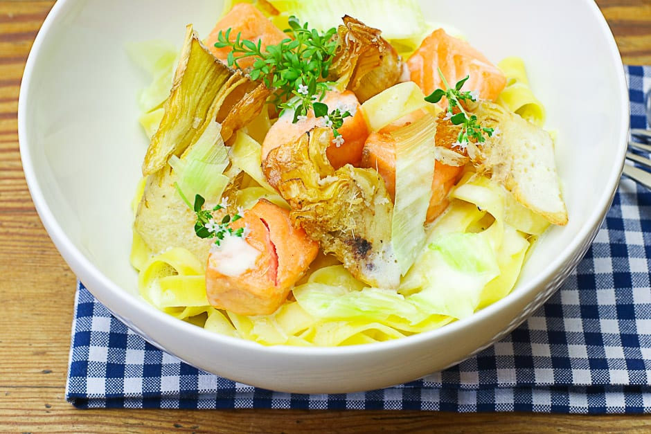 Salmon noodles with lemon sauce, and artichokes served in a bowl.