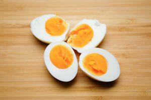 Gekochte, geschälte und halbierte Eier auf einem Küchenbrett