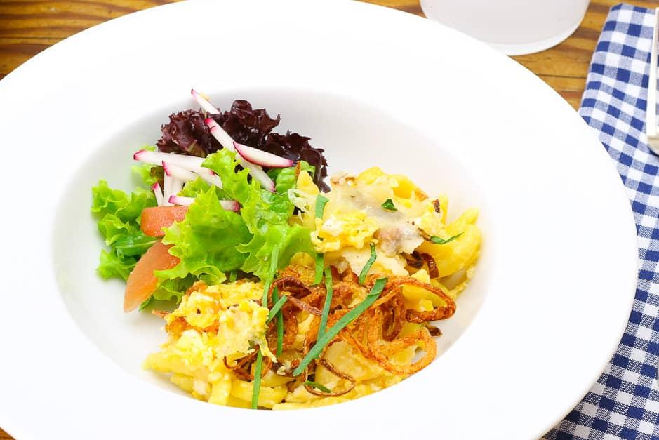 Käsespätzle nahaufnahme, angerichtet mit Salat.