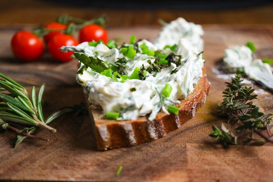 Kräuterquark auf dem Brot mit Umfeld nah fotografiert.