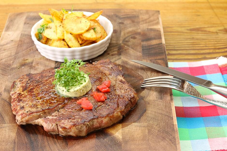 Rib eye steak served with fried potatoes.