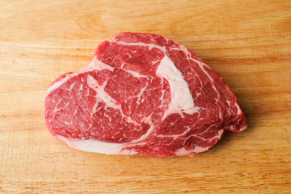 Rib Eye Steak raw on a kitchen board