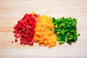 Gewürfeltes Gemüse auf einem Brett.
