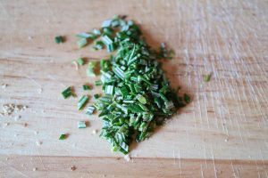 Rosemary needles finely chopped on a kitchen board.