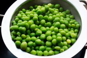 Frische, gekochte, grüne Erbsen auf einem Küchensieb.