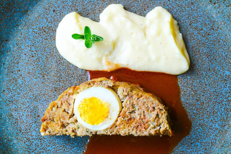 Hackbraten mit Ei, Soße und Kartoffelpüree auf einem blauen Teller.
