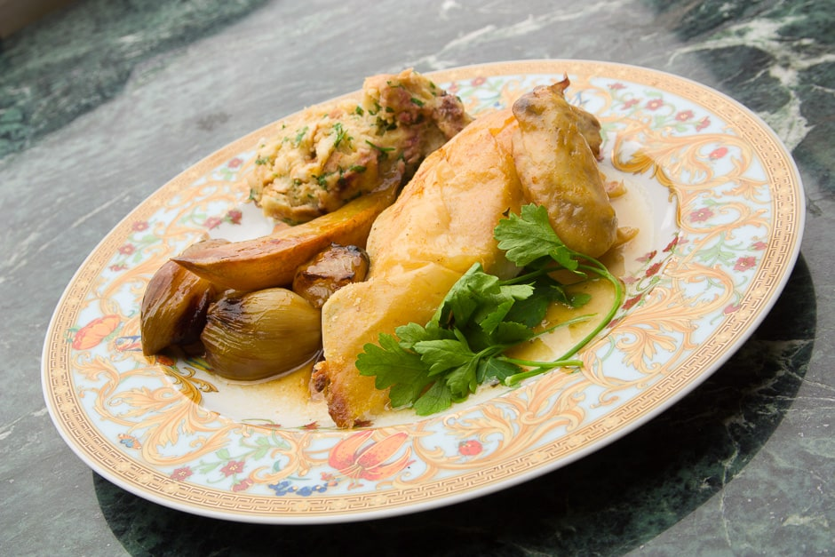 Roast chicken with crispy skin and side dishes served on a plate.