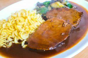 Rinderbraten mit Soße und Beilage heiß anrichten.