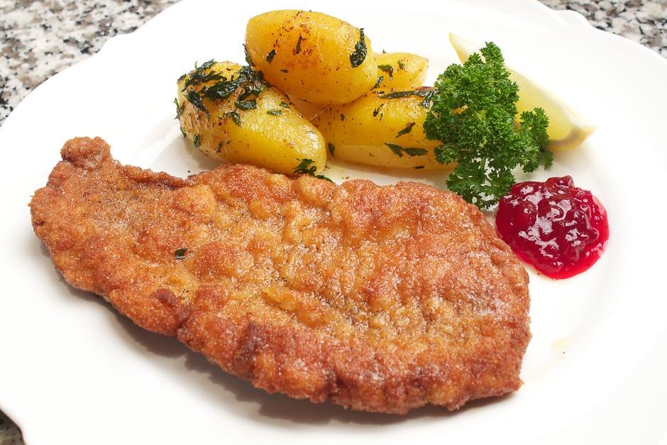 Wiener Schnitzel auf dem Teller angerichtet mit Prieiselbeeren und Petersilienkartoffeln.