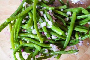 Bohnensalat mit Zwiebeln marinieren.