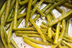 Blanchierte Bohnen im Topf mit Butter