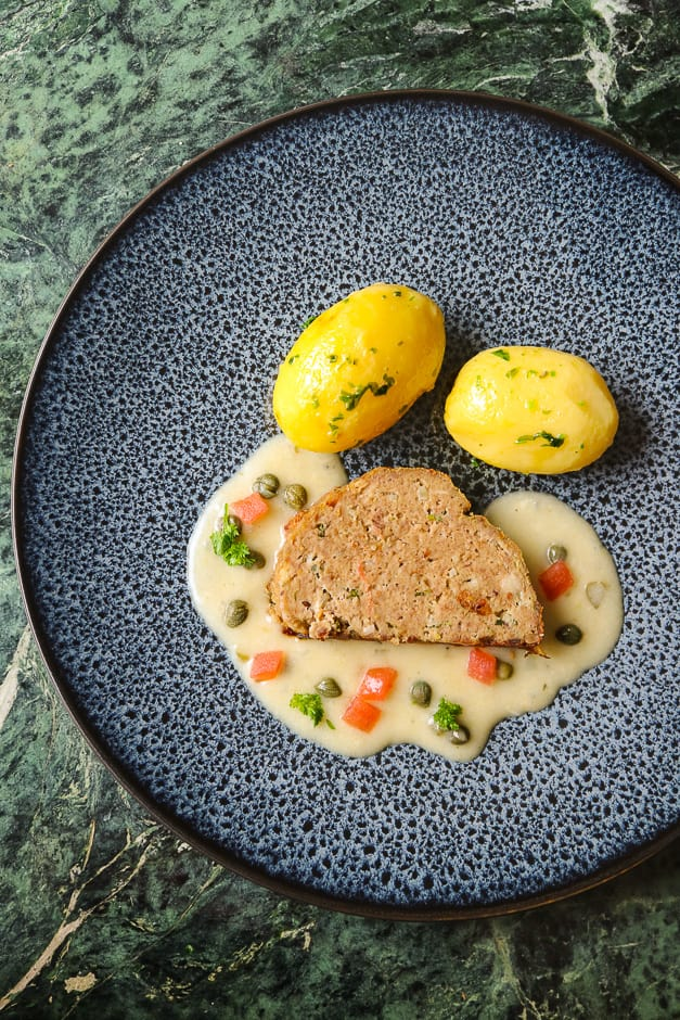 Meat loaf without filling served with caper sauce, tomato cubes, potatoes and parsley.