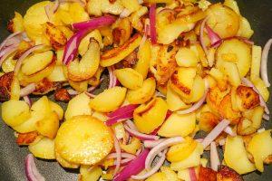 Zwiebeln zu den Kartoffeln geben.