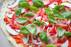 Pizza mit Gemüse belegen